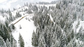 AERIAL: Car driving along the forest road in winter. Winter Carpatians nature, aerial view realtime snowfall, UHD 4K stock video footage