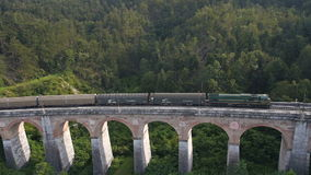 Aerial: cargo train crosses the old stone railroad bridge stock video footage