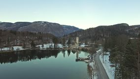 Aerial: Cars Driving By The Beautiful Winter Lake In Bohinj, Slovenia At Winter. Drone Shot Of Cars Driving By The Beautiful Winter Lake In Bohinj, Slovenia At stock video footage