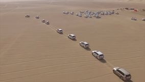 AERIAL: cars driving through desert. Stock. Aerial view of 4x4 off road land vehicle taking tourists on desert dune. AERIAL: cars driving through desert. Aerial stock photography