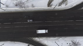 Aerial - Cars driving on six-lane road through a snowy landscape. Aerial - Cars driving on a two-lane road through a snowy landscape. 4k video stock footage