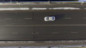 Aerial - Cars driving on two-lane road through a snowy landscape stock footage