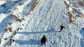 Aerial. children are riding on sleds on a snow-covered hill stock video footage