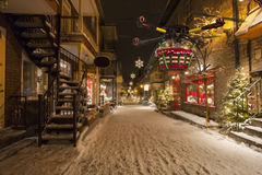 Aerial Christmas Delivery 2. A flying quadrocopter delivering a basket of Christmas goodies above covered with snow beautifully decorated street Royalty Free Stock Image