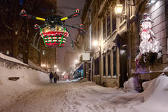 Aerial Christmas Delivery 3. A flying quadrocopter delivering a basket of Christmas goodies above covered with snow beautifully decorated street Royalty Free Stock Images