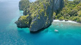 Aerial circle fly above coral reef and banca boats at the beach of limestone rocky Entalula Island, Bacuit Bay, El-Nido stock video