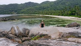 Aerial circling footage of blonde girl relaxing in yoga pose on granite rock surrounded by exotic tropical island with stock footage