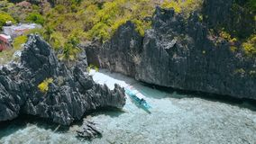 Aerial circling movement around Matinloc Shrine. El Nido, Palawan, Philippines. Bizarre limestone rocks and lonely boat. In shallow water with colorful coral stock video footage