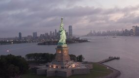 AERIAL: Circling Statue of Liberty beautifully illuminated in early morning light New York City
