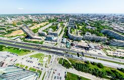 Aerial city view with crossroads and roads, houses, buildings, parks and parking lots. Sunny summer panoramic image Royalty Free Stock Photo