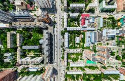 Aerial city view with crossroads and roads, houses, buildings, parks and parking lots. Sunny summer panoramic image. Aerial city view with crossroads and roads Royalty Free Stock Photography