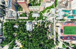 Aerial city view with crossroads and roads, houses, buildings, parks and parking lots. Sunny summer panoramic image Royalty Free Stock Photography