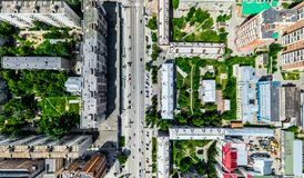 Aerial city view with crossroads and roads, houses, buildings, parks and parking lots. Sunny summer panoramic image Stock Photography