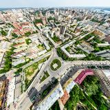 Aerial city view with crossroads and roads, houses, buildings, parks and parking lots. Sunny summer panoramic image Stock Photos