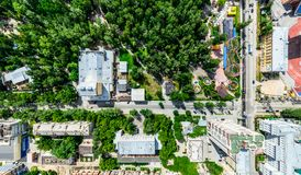 Aerial city view with crossroads and roads, houses, buildings, parks and parking lots. Sunny summer panoramic image Royalty Free Stock Photos