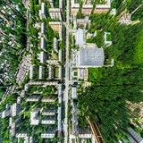 Aerial city view with crossroads and roads, houses, buildings, parks and parking lots. Sunny summer panoramic image Stock Image