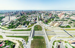 Aerial city view with crossroads and roads, houses, buildings, parks and parking lots. Sunny summer panoramic image. Aerial city view with crossroads and roads Stock Photos