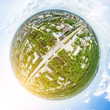 Aerial city view with crossroads and roads, houses, buildings, parks and parking lots. Sunny summer panoramic image Stock Images