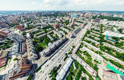 Aerial city view with crossroads and roads, houses, buildings, parks and parking lots. Sunny summer panoramic image. Aerial city view with crossroads and roads Stock Photo