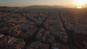 Aerial cityscape of Barcelona at sunset. Flying over Barcelona at sunset, Spain. Streets and houses in warm light of evening sun stock video