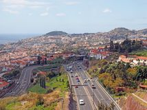An aerial cityscape view of funchal showing traffic on the main VR1 motorway running into the city with the coast visible in the. Distance stock photo