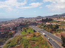 an aerial cityscape view of funchal showing traffic on the main VR1 motorway running into the city with the coast visible in the stock photography