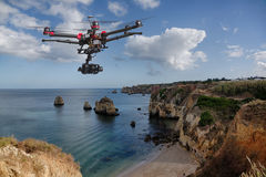 Aerial cliffs patrol. A drone with raised landing gears and a camera flying in beautiful cloudy skies along spectacular sea cliffs with a calm ocean in the Stock Image