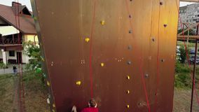 Aerial of climber runs the speed rock climbing track on artificial wall outdoors. Young fast athlete climbs the cliff at
