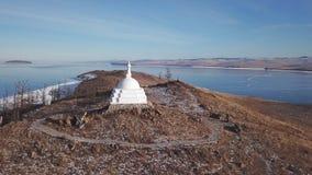 Aerial Close Unique Buddhist stupa historic monument symbol spire top mystical ritual costal Ogoi Island Lake Baikal. Rock Burkhan landscape mountains Shamanic stock footage