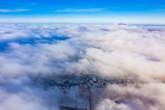 Aerial cloudscape. Flying above city on sunny day stock photo