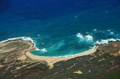 Aerial of coastline of Molokai with waves crashing into Mo'omomi. Beach, rocky shore and surrounding area of island with dirt roads, largely undeveloped. April Royalty Free Stock Images