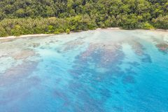 Aerial of Coral Reefs and Island in Papua New Guinea. A bird`s eye view of the remote island of New Ireland in Papua New Guinea shows reef growth along the royalty free stock photo