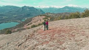 Aerial: couple hiking on the mountains, backpackers walking outdoors panoramic view, inspiring travel and freedom, drone flight re stock video
