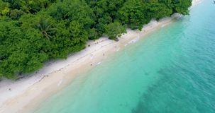 Aerial: A couple walks along the beach with white sand and turquoise water. stock video