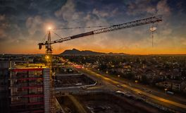 Aerial of crane sunset. Aerial of crane looking over road and building sunset Stock Images