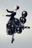 Aerial dancer. Studio photo of a young ballet dancer flying away on balloons Royalty Free Stock Images