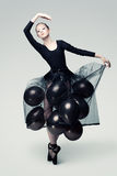 Aerial dancer. Studio photo of a young ballet dancer flying away on balloons Royalty Free Stock Photos
