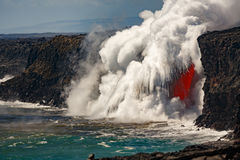 Aerial daytime view of top portion of waterfall shaped flow of red lava from volcano in Hawaii exploding into the sea Stock Photography
