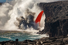 Aerial daytime view of wide waterfall  shaped flow of red lava from volcano in Hawaii exploding into  sea Stock Photo