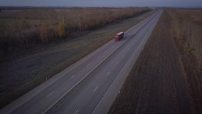 AERIAL: Delivery trucks driving towards the sun. the car with the container rides on the road to the sunset. Truck rides stock footage