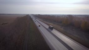 AERIAL: Delivery trucks driving towards the sun. the car with the container rides on the road to the sunset. Truck rides. The highway stock video footage