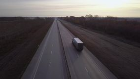 AERIAL: Delivery trucks driving towards the sun. the car with the container rides on the road to the sunset. Truck rides. The highway stock video