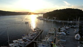 Aerial: descending above sailboats moored in marina of adriatic sea at sunset stock footage
