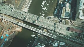 Aerial down view of cars moving along the bridge across icy river