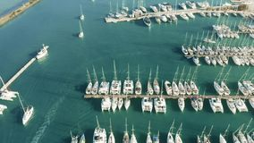 Aerial down view of docked sailing yachts and catamarans in marina. Aerial down shot of docked sailing yachts in marina stock video footage