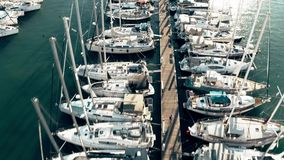 Low altitude aerial down view of a marina pier and many docked sailing yachts. Aerial down view of a marina pier and docked sailing yachts stock video footage