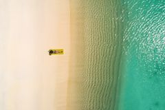 Aerial drone aerial view of Beautiful girl having fun on the sunny tropical beach. Seychelles.  royalty free stock image