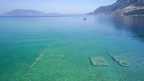 Aerial drone bird`s eye view photo of tourists snorkeling above old Sunken City of Epidauros, Greece