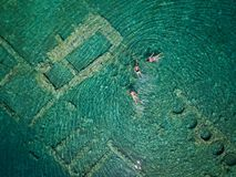 Aerial drone bird`s eye view photo of tourists snorkeling above old Sunken City of Epidauros, Greece royalty free stock image