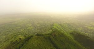 Aerial drone bird`s eye view video on a beautiful mountain covered with green grass. On top of the mountain there is a. Aerial drone bird`s eye view video on a stock footage